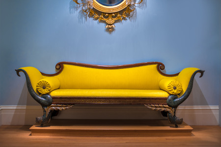 leathern: Luxury yellow sofa in front of the blue wall Stock Photo