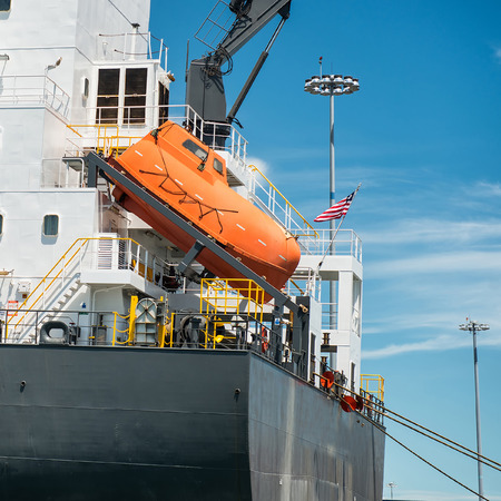 freefall: orange free-fall life boat for emergency crew evacuation installed on cargo ship