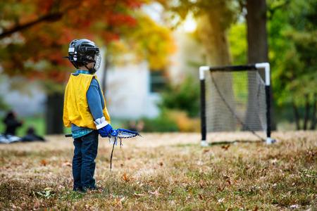juventud: Niño que juega con su palo de lacrosse en el parque del otoño