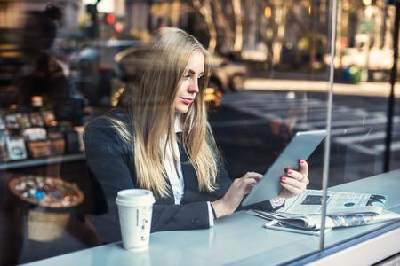 periodicos: Mujer de negocios que se sienta en café y que usa la PC de la tableta y el consumo de café Foto de archivo