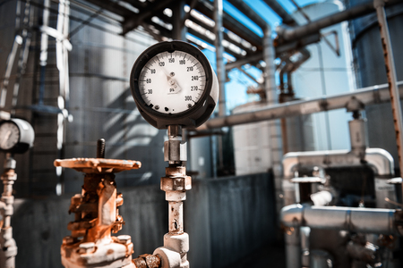 manometer: Closeup of manometer, measuring gas pressure. Pipes and valves at industrial plant.