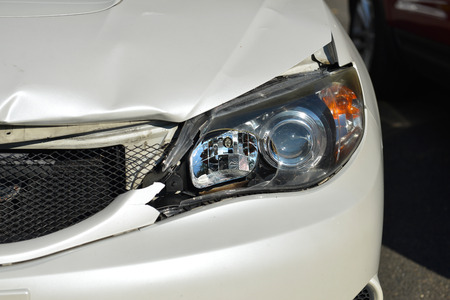 fatality: Broken front headlight on white car Stock Photo