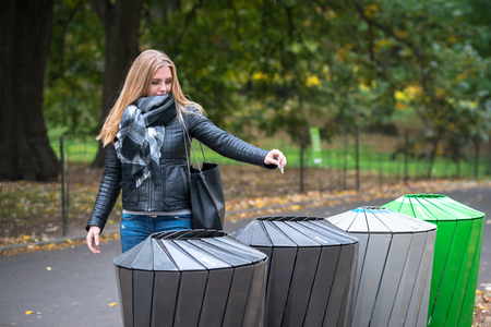 Woman throws recycle paper trash in the trash sorting waste