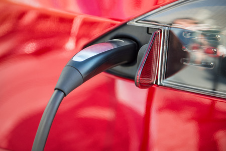 plugged in': electric car charging process by power cable supply plugged in