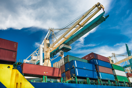 container port: port crane unloads freight cargo ship with containers