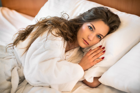 house robe: Beautiful woman lying on the bed in white bathrobe