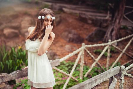 Schöne zarte Frau mit Blume im Kopf in der Natur aufwirft