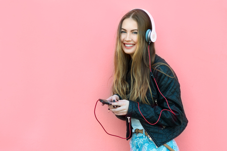 listening device: beautiful happy woman in headphones listening music near the wall Stock Photo