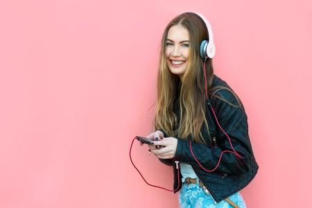 personas escuchando: hermosa mujer feliz en los auriculares escuchando música cerca de la pared