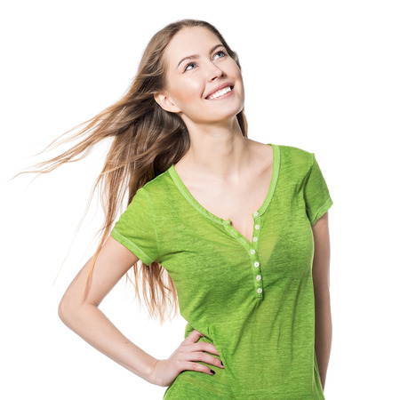 Beautiful smiling woman in green t-shirt looking up isolated on white Stock Photo