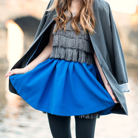 woman street fashion look with blue skirt, jacket, dress and black tights Stockfoto