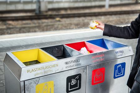 reciclar basura: La mujer lanza la basura de papel en la clasificaci�n de residuos de basura