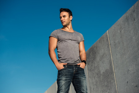 Handsome bearded fashion model man posing outdoors wearing grey t-shirt and jeans Stok Fotoğraf
