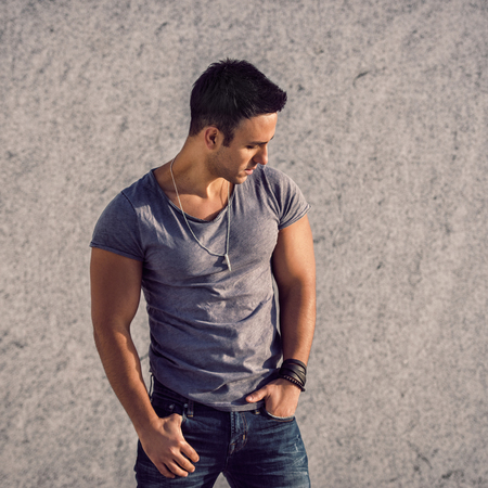 Portrait of fashion model man wearing grey t-shirt and jeans posing in front of the wall