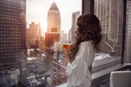 コーヒー カップを保持している、豪華なマンハッタンのペントハウス ・ アパートメントでウィンドウを探している美しい女性。