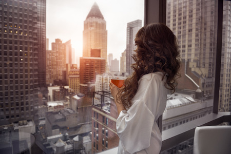 Beautiful woman holding coffee cup and looking to the window in luxury Manhattan penthouse apartments. 免版税图像