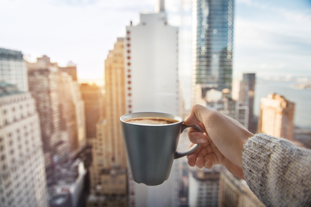 Man holding coffee cup in luxury penthouse apartments with view to New York City Manhattan downtown at the morning Stock Photo