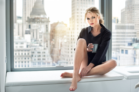 penthouse: Beautiful woman drinking coffee at the mornig in luxury city penthouse