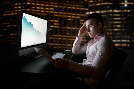 negative equity: Stock analityc and broker looking at stock charts going down after sales report Stock Photo
