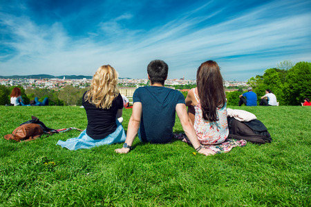 frienship: Three tourists friend sitting on the green grass with beautiful view to Vienna panorama Stock Photo