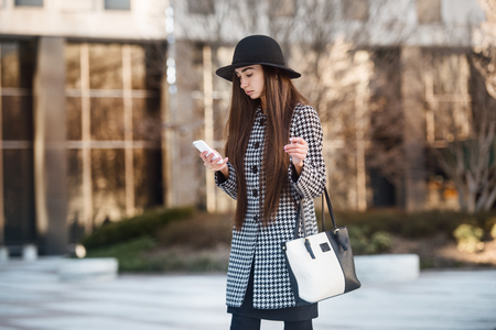 Beautiful business woman using smartphone and walking near office building on city street Stock Photo