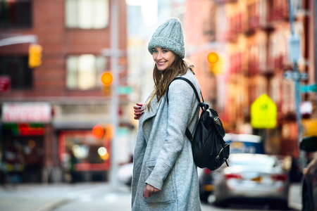 Beautiful happy woman walking on the city street wearing casual grey coat and hat with a bag