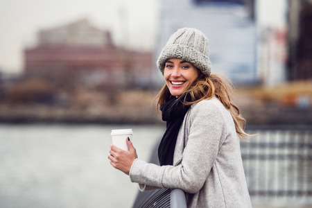 Beautiful smiling woman drinking coffee from paper cup standin on river embankment and enjoing the view Stock Photo