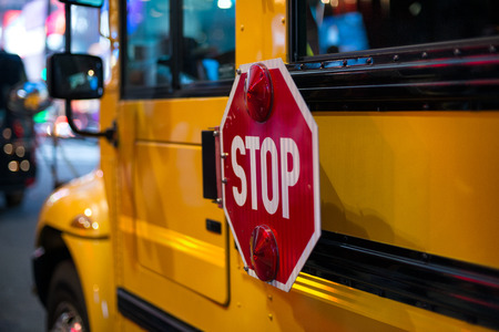 Stop sign on side on yellow School Bus Stock Photo
