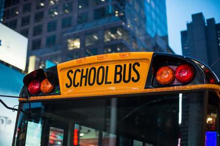 flashers: School bus children educational transport sitting in the parking at the night  in New York City street