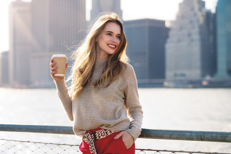 Beautiful woman holding paper coffee cup and enjoying the walk in the city