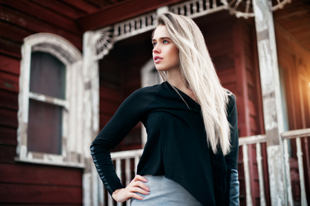 Beautiful blonde hair girl standing near red vintage house at sunset time and looking to the side