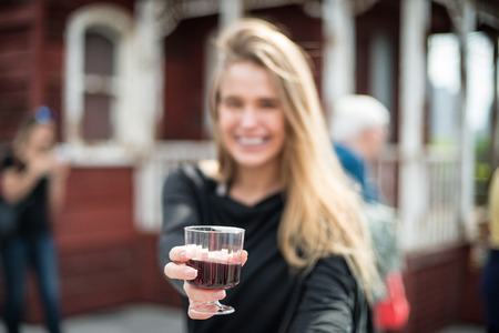 outoors: Happy woman drinking alcohol outoors on the party event. Focus on wine glass