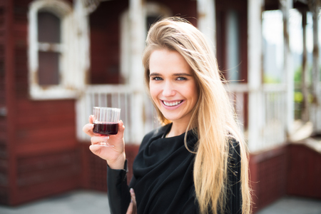 syrah: Beautiful young woman drinking wine and smiling standing outdoors near the house Stock Photo