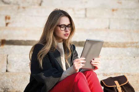 Gorgeous student girl sitting on stair wearing eyeglasses and reading ebook on tablet Stock Photo