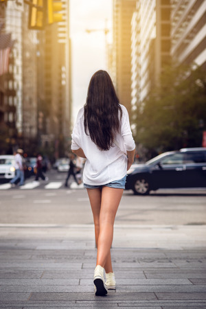 legs around: Beautiful girl with long legs walking around New York City street wearing jeans shorts. Rear view.