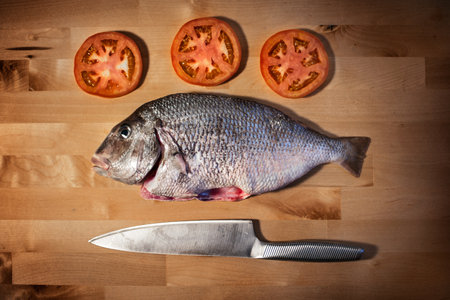 gilt head: Delicious fresh sea bream fish on wooden kitchen board with tomatos