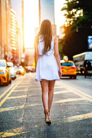 Beautiful girl wearing white mini dress and walking on New York City street making step on traffic lane in city at sunset time.