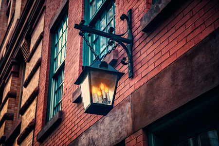 old town house: Black old vintage lamp on brick wall with decorative candles inside at old town house. Stock Photo