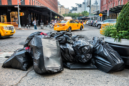 camion de basura: Black bags of trash on sidewalk in New York City street waiting for service trash truck. Garbage packed in big trash bags ready for transportation.