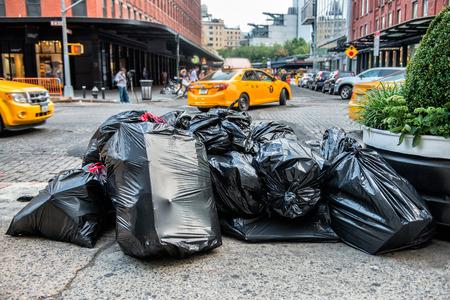 camion de basura: bolsas negras de basura en la acera de la calle en la ciudad de Nueva York en espera de cami�n de servicio de basura. Basura empaqueta en bolsas grandes de basura listo para el transporte. Foto de archivo