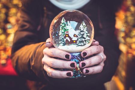 Woman holding snow globe on the Christmas fair