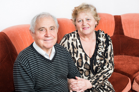 close together: Happy senior couple sitting close together on a sofa in the house smiling