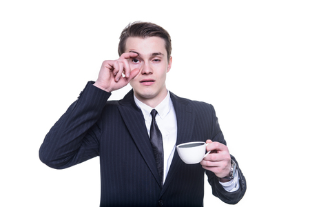 deprived: businessman tired and falling asleep drinking a cup of coffee