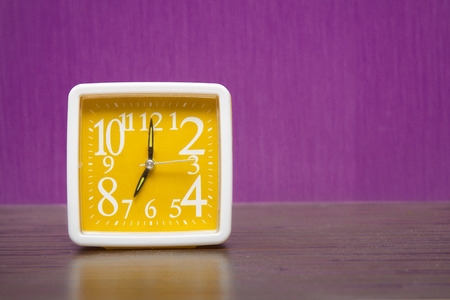 wood tick: alarm clock on a wooden table in front of purple wall