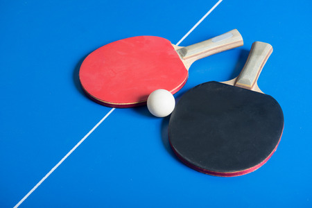 pong: Pin pong ball with red paddle on blue board