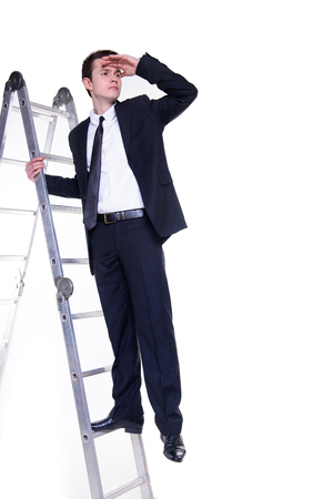 searching for: Young businessman on a ladder searching for possibilities
