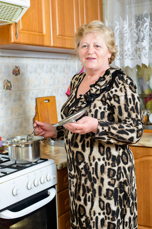 oap: Senior woman cooking at the kitchen Stock Photo