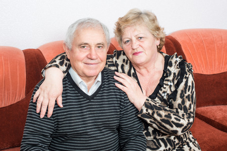 camaraderie: Happy senior couple sitting close together on a sofa in the house