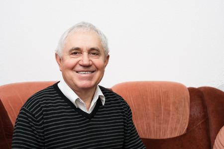Portrait of senior man sitting on sofa