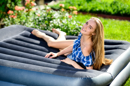 Happy young woman lying on the matrass in the garden